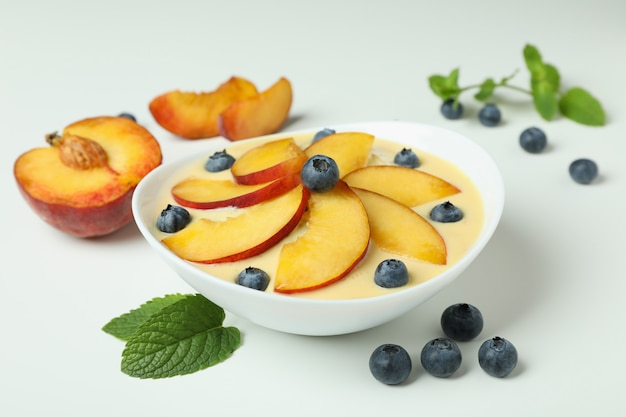 白い背景の上の桃のヨーグルトと材料