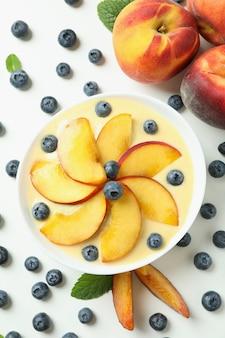 Peach yogurt and ingredients on white background