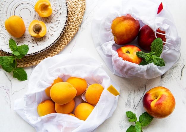 Персики и абрикосы в эко-пакетах. концепция нулевых отходов.
