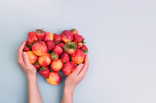Персики и клубника в руках женщины на голубой стене. copyspace. композиция в форме сердца.