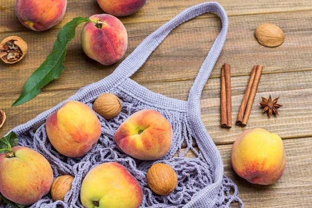 Персики и грецкие орехи в серой тканевой сетке. персики и палочки корицы на столе. деревянный фон. плоская планировка