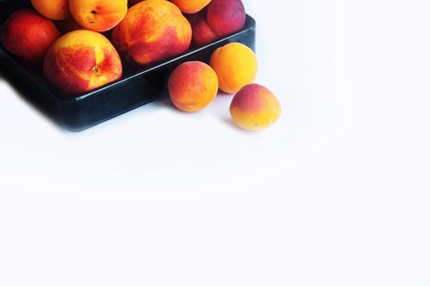 Персики, абрикосы и нектарины в черной тарелке на белом фоне