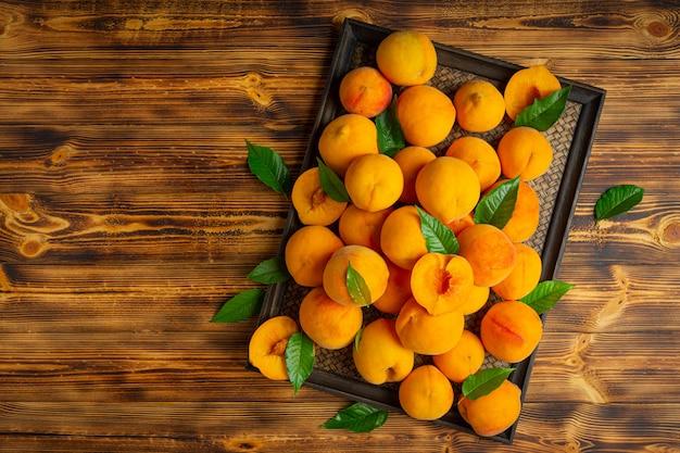 Персики выложены на деревянную доску.