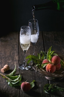 Peaches on branch with champagne