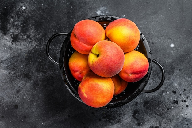 Peaches fruit in a black colander on the table. black background. top view.