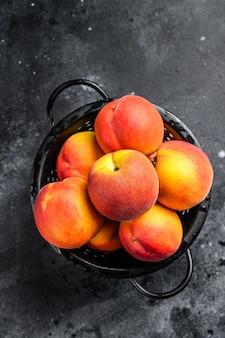 テーブルの上の黒いザルで桃の果実