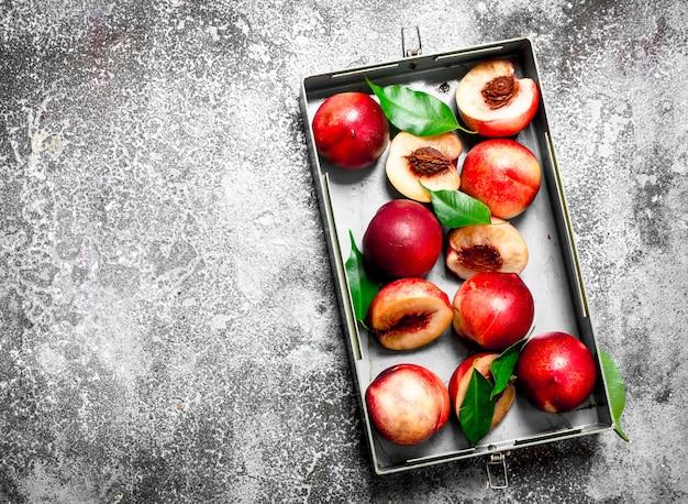 Персики в коробке. на деревенском столе.