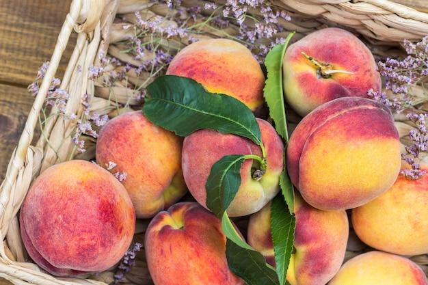 Персики в плетеной корзине. деревянный фон. плоская планировка