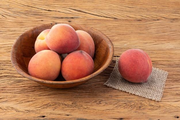 木製のテーブルの上のボウルに桃。