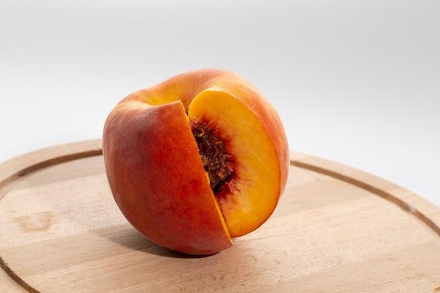 Персики на деревянной доске. персик пополам с косточкой. спелые сочные фрукты