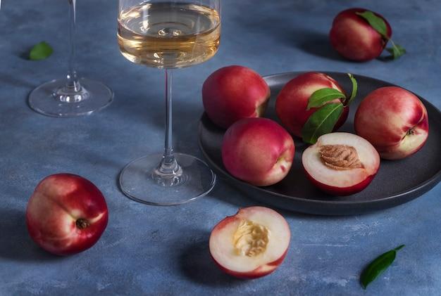 Персики или нектарины на черной керамической тарелке и бокале белого вина