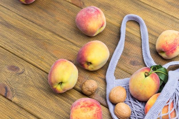 生地のメッシュバッグに緑の葉が付いた桃。スペースをコピーします。木製の背景。上面図