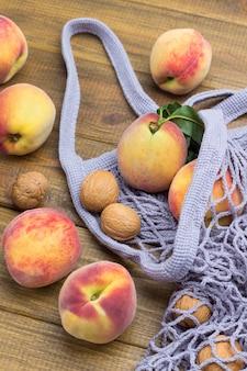 生地のメッシュバッグに緑の葉が付いた桃。木製の背景。上面図