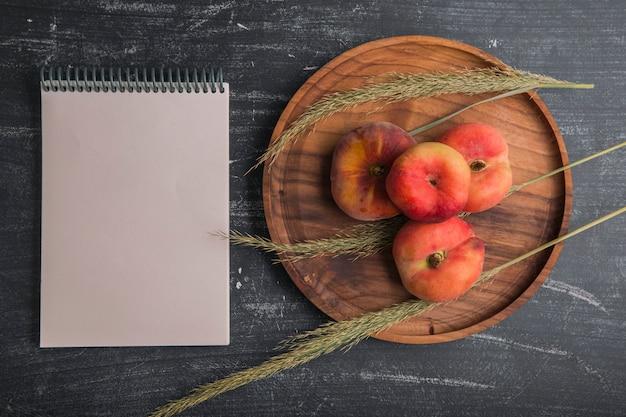 ハーブまたはスパイスとノートを脇に木製の大皿に桃