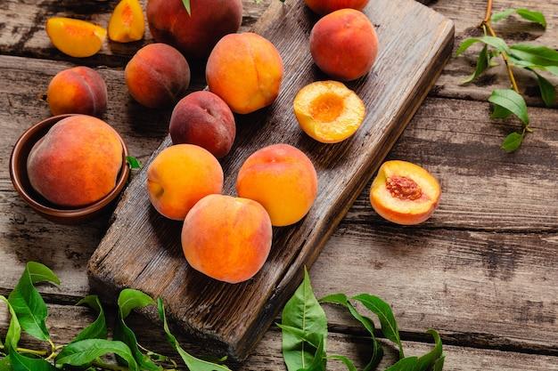 Персики с листьями на деревянной доске с персиком пополам. плоская композиция со спелыми сочными персиками. урожай персиков для еды или сока. вид сверху свежие органические фрукты с копией пространства.
