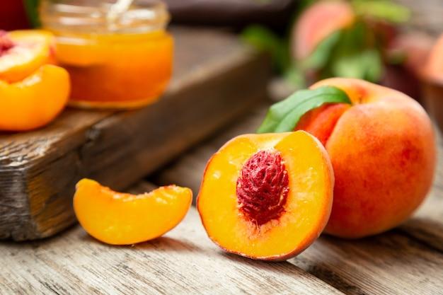 桃の種の石で半分に桃と暗い木の板に葉を持つ桃。熟したジューシーな桃を使った組成食品の収穫。新鮮な有機フルーツ。