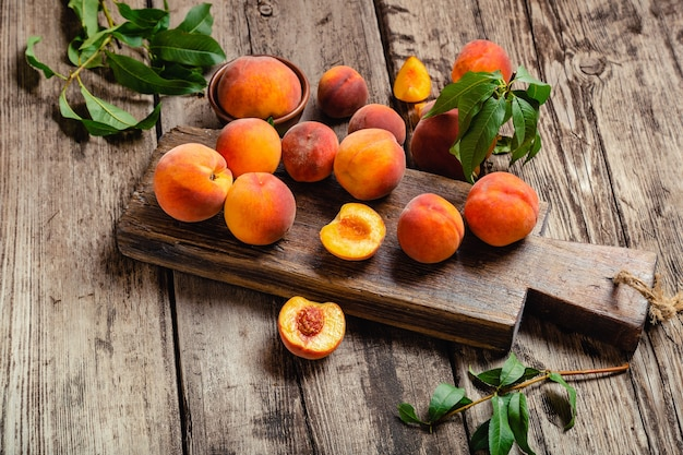 Peaches with leaves on wooden table with peach in halves ripe juicy peaches harvest of peaches