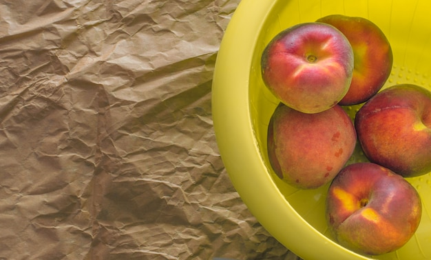 Peaches in a yellow plastic cup on a brown paper