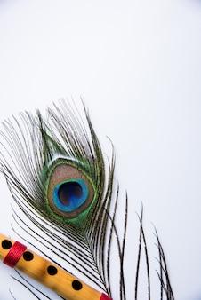 화려한 배경 위에 공작 깃털과 대나무 피리