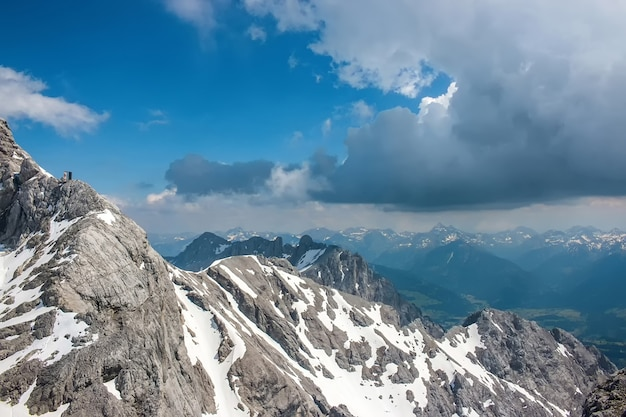 On peak of dachstein and view alpine mountains. national park in austria, europe. blue and cloudy sky in summer day