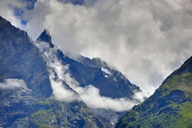 Пик горы с ледниками на фоне облаков и неба