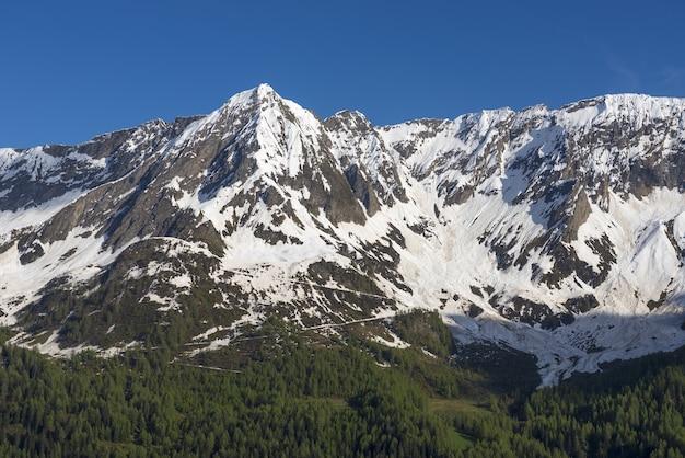 スイス、ティチーノ州の青い空を背景に雪に覆われた山々の頂上