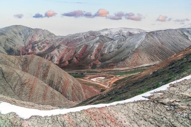 赤い山々の頂上は雪に覆われ、冬の高原の風景