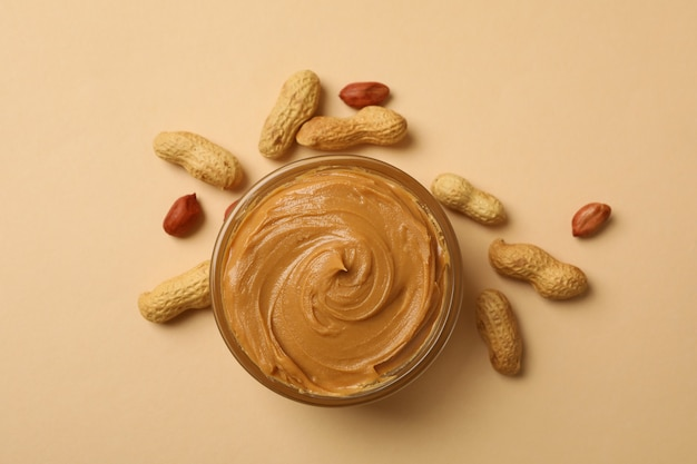 Peanut and bowl with peanut butter on beige background