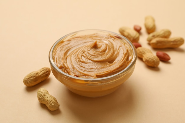 Peanut and bowl with peanut butter on beige background Premium Photo