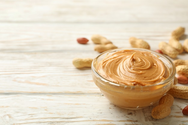 Peanut and bowl with peanut butter on wooden background