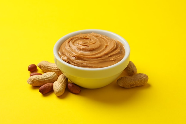 Peanut and bowl with peanut butter on yellow background