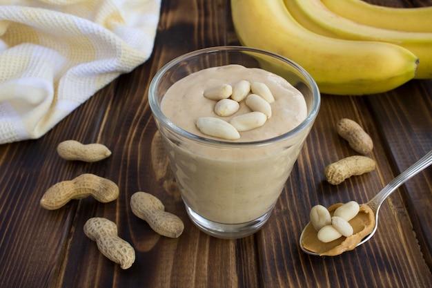 ピーナッツバターバナナは茶色の木製の背景のガラスでシェイク