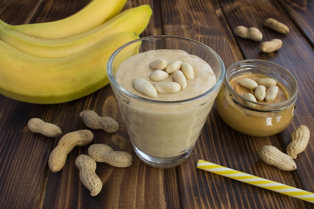 ピーナッツバターバナナは茶色の木のガラスで振る