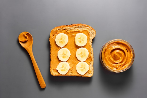 Peanut butter and banana toast over grey background. top view.