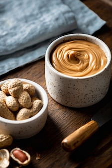 Peanut butter in a ceramic bowl on wooden background