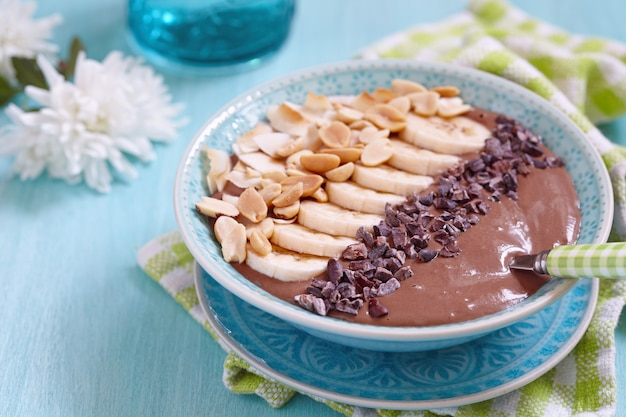 Peanut butter chocolate smoothie with banana and nuts topping