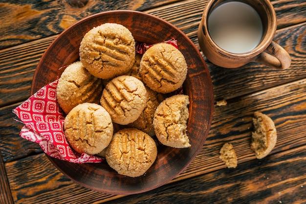 木製の背景にミルクとピーナッツバタークッキーと粘土マグカップ