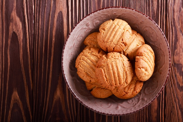 木製の背景上にボウルにピーナッツバタークッキー