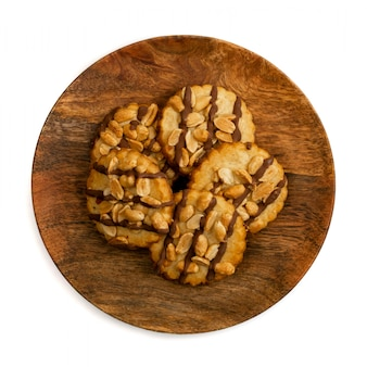 Peanut butter cookies with dark chocolate on wooden plate isolated on white background. fresh homemade nutty crackers top view and close up