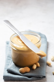Peanut butter in a glass jar and knife on the table
