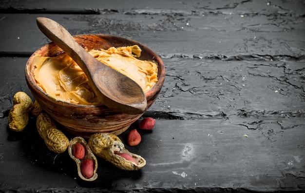 素朴なテーブルの上に木のスプーンでボウルにピーナッツバター。