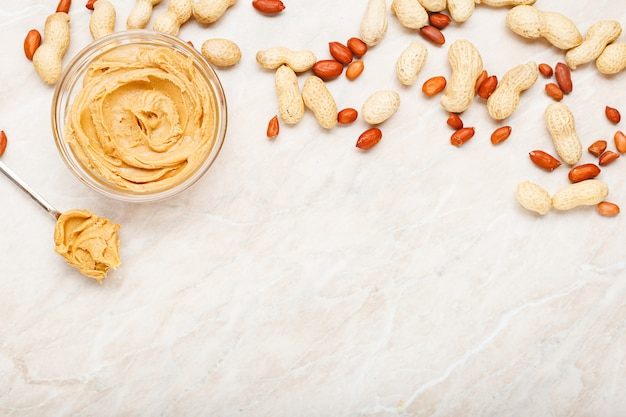 Арахисовое масло в стеклянной тарелке с арахисом в скорлупе, очищенным арахисом, ложкой с арахисовой пастой. плоская планировка с местом для текста на белом мраморном фоне