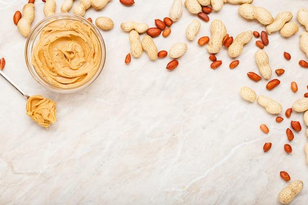 껍질에 땅콩이 있는 유리 접시에 땅콩 버터, 껍질을 벗긴 땅콩, 땅콩 버터가 든 빈티지 스푼. 아침 식사를 위해 흰색 대리석 배경에 텍스트를 넣을 수 있는 평평한 땅콩 페이스트