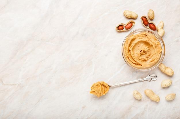 Арахисовое масло в стеклянной пластине с арахисом в скорлупе, очищенный арахис, старинные ложки с арахисовым маслом. сладкая арахисовая паста плоское положение с местом для текста на фоне белого мрамора для приготовления завтрака.
