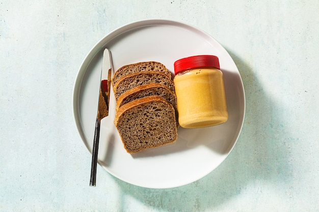Peanut butter in a jar and whole grain bread with a knife on the table.