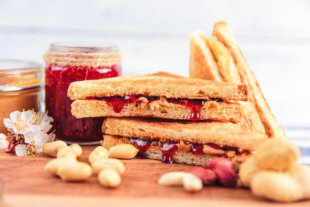 Peanut butter and raspberry jam near peanuts and sandwiches