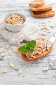 Peanut butter sandwich. decorated with mint. in the background is a cup with peanut butter and bread.
