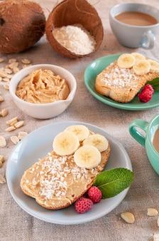 Сэндвич с арахисовым маслом. украшается дольками банана, малиной, мятой и кокосовой стружкой.