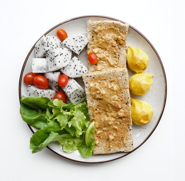白い背景の上のドラゴンフルーツチェリートマトと野菜とピーナッツバターのサンドイッチ