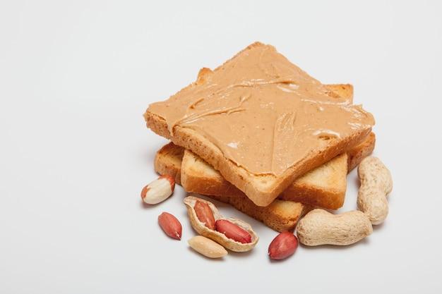 白地にピーナッツバターのサンドイッチまたはトースト